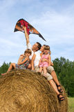 The happy family astride hay flying kite. Stock Image