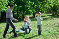 A family of four people are allowed to make soap bubbles. Royalty Free Stock Photos