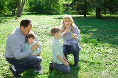 A family of four people are allowed to make soap bubbles. Royalty Free Stock Image