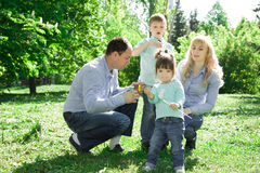 A family of four people are allowed to make soap bubbles. Royalty Free Stock Photography