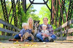 Family of Four People and Dog Sitting On Bridge in Autumn Royalty Free Stock Images