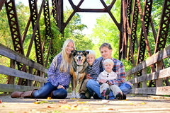 Family of Four People and Dog Sitting On Bridge in Autumn Royalty Free Stock Photo