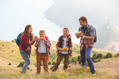 Family of four people eating fastfood in mountains Royalty Free Stock Photos