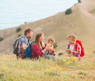 Family of four people eating fastfood in mountains Stock Photos