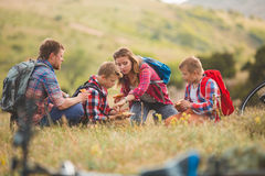Family of four people eating fastfood in mountains Royalty Free Stock Image