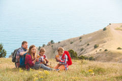 Family of four people eating fastfood in mountains Stock Photo