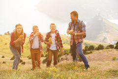 Family of four people eating fastfood in mountains Royalty Free Stock Photography