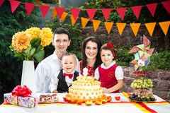 Family of four people father mom son and daughter celebrates daughter`s birthday three years sitting at a festive decorated table. Decor and a big delicious Stock Image