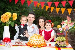 Family of four people father mom son and daughter celebrates daughter`s birthday three years sitting at a festive decorated table. Decor and a big delicious Royalty Free Stock Photos