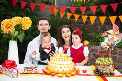 Family of four people father mom son and daughter celebrates daughter`s birthday three years sitting at a festive decorated table. Decor and a big delicious stock images