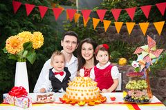 Family of four people father mom son and daughter celebrates daughter`s birthday three years sitting at a festive decorated table. Decor and a big delicious stock photos