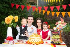 Family of four people father mom son and daughter celebrates daughter`s birthday three years sitting at a festive decorated table. Decor and a big delicious royalty free stock photo