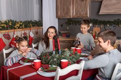 A family of four in identical sweaters sit at the Christmas table and the boy pours tea in the New Year`s decorated kitchen royalty free stock image