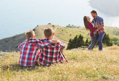Family of four people looking to beautiful seascape in mountains Royalty Free Stock Images