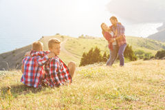 Family of four people looking to beautiful seascape in mountains Stock Photo
