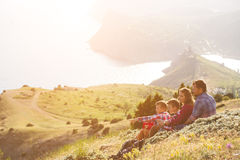 Family of four people looking to beautiful seascape in mountains Stock Image