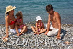 Family from four persons has rest on beach. Girl observes as daddy spreads from stones word summer Royalty Free Stock Photography