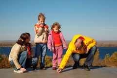 Family from four persons walks in solar autumn day. Parents draw chalk on asphalt Stock Photos