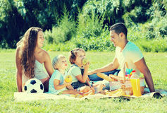 Family of four on picnic. Positive happy smiling family of four on picnic in park at summer day stock images