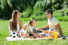 Family of four on picnic. Positive happy smiling family of four on picnic at summer day royalty free stock images