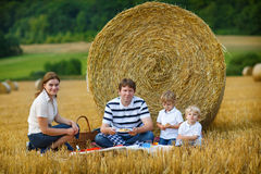 Family of four picnicking on yellow hay field in summer. Royalty Free Stock Photo