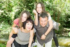 Family of four play piggy back outdoor in love royalty free stock photos