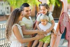 Family of four at playground Stock Photos