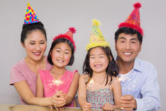 Family of four playing with firecrackers at a birthday party. Portrait of a family of four playing with firecrackers at a birthday party royalty free stock photos