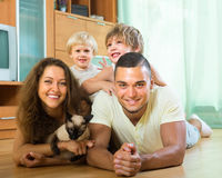 Family of four playing with kitten Royalty Free Stock Images