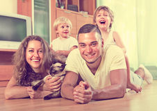 Family of four playing with kitten Stock Photo