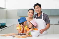 Family of four preparing cookies in kitchen Royalty Free Stock Photo