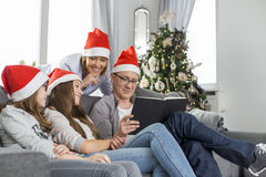 Family of four reading book in living room during Christmas Stock Image