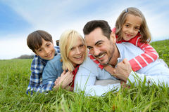 Portrait of happy family laying in field Royalty Free Stock Photo