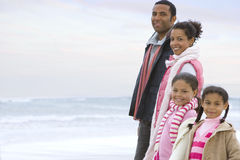 Family of four in row on beach, smiling, portrait Stock Photography