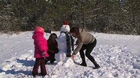 Family of four run around upside down snowman at winter day. Three girls dancing around a snowman. This occurs in a clearing near the forest stock video