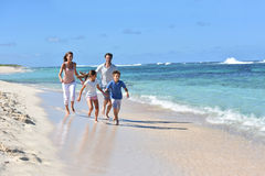 Family of four runinng on the beach in tropics Royalty Free Stock Photo