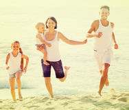 Family of four running on sandy beach on sunny weather Royalty Free Stock Image