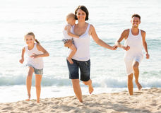 Family of four running on sandy beach on sunny weather Royalty Free Stock Photo