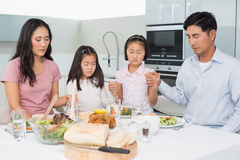 Family of four saying grace before meal in kitchen. Family of four saying grace before meal in the kitchen at home Royalty Free Stock Photography