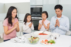 Family of four saying grace before meal in kitchen. Family of four saying grace before meal in the kitchen at home Royalty Free Stock Photo