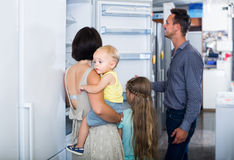 Family of four shopping new refrigerator in home appliance store stock images