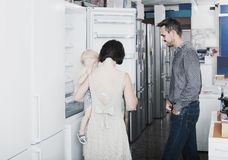 Family of four shopping new refrigerator in home appliance store Stock Photos
