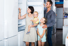 Family of four shopping new refrigerator in home appliance store. Smiling spanish family of four shopping new refrigerator in home appliance store royalty free stock images