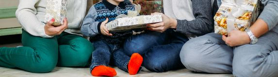 A family of four sit on the floor near the tree and exchange gifts. unfold gifts stock images