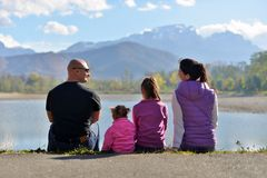 A family of four sit near the lake on the background of mountains. royalty free stock photography