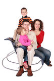Family of four sits on chair Stock Photo