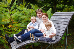 Family of four sitting on a bench in autumn park Stock Photos