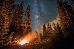 Family of four sitting by a glowing campfire under the milky way, Utah, USA. Family of four by a glowing campfire under the milky way and starry skies, Utah stock images