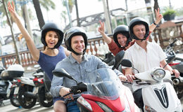 Family of four sitting on scooter in city street Stock Images