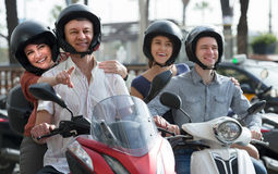 Family of four sitting on scooter in city street Stock Photography